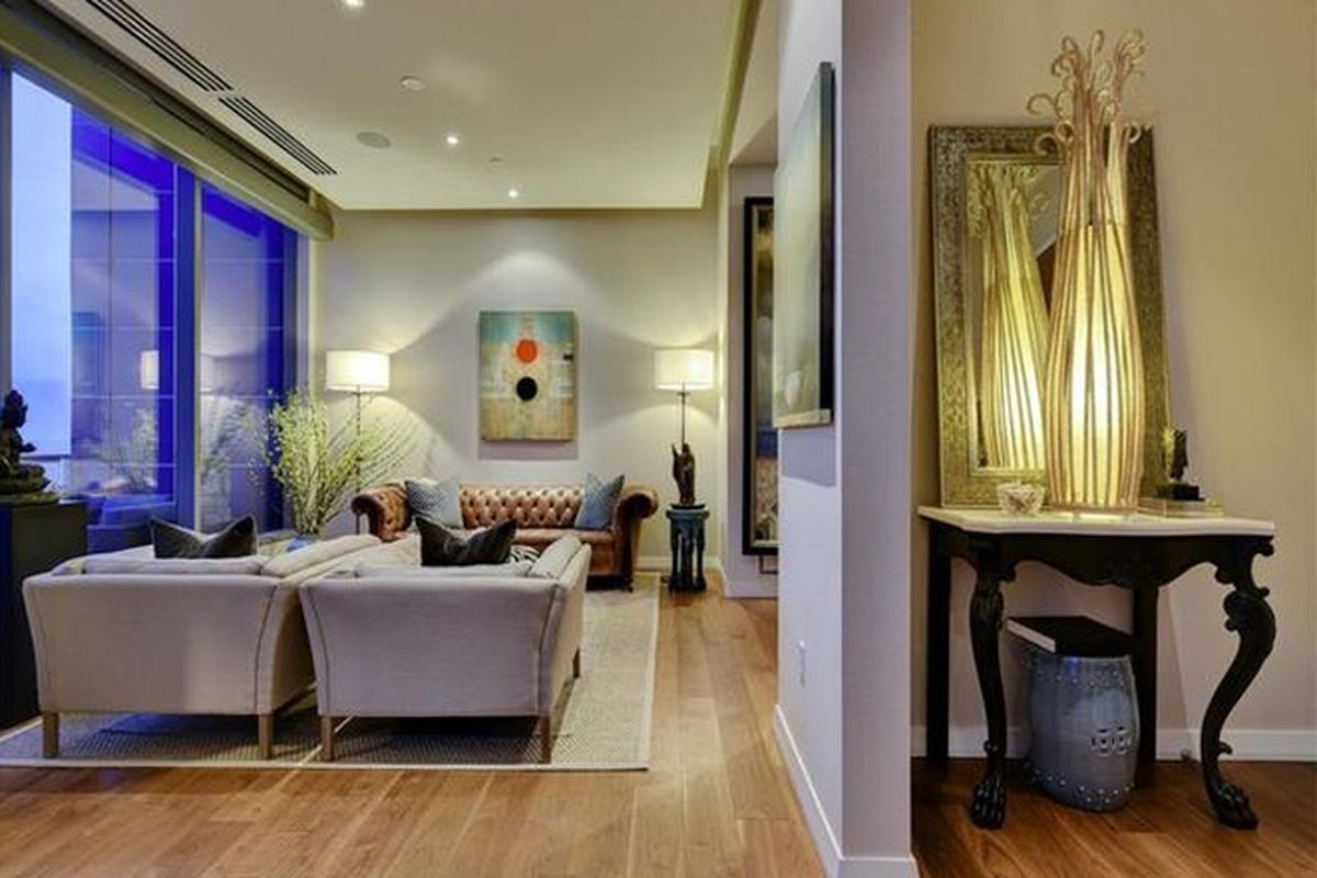 High-rise condo living room with light chairs, window-wall view of downtown, spots of color in in art on walls