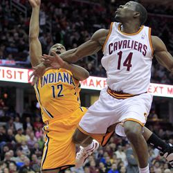 Indiana Pacers' A.J. Price (12) takes an off-balance shot against Cleveland Cavaliers' Lester Hudson (14) in the first half of an NBA basketball game Wednesday, April 11, 2012, in Cleveland.