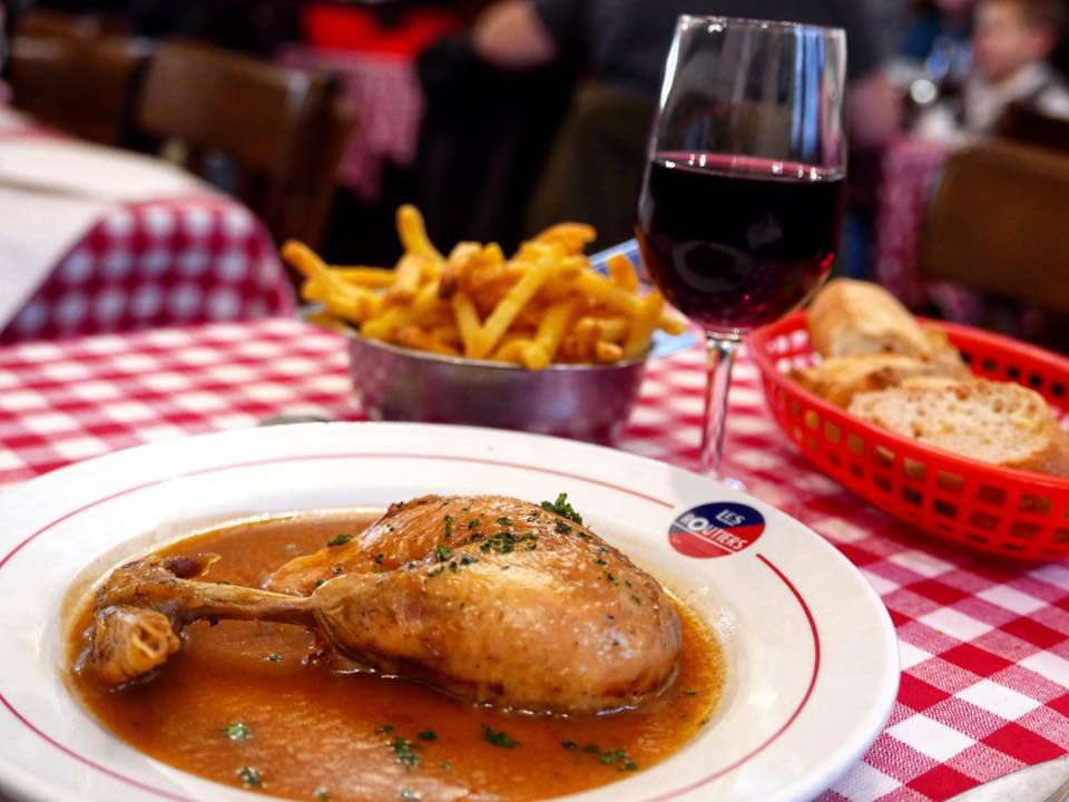A leg of roast chicken in sauce beside a glass of wine, metal tin of fries and basket of bread, all on a checkered tablecloth