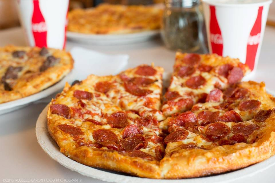 small pepperoni pizza with Coke cups in the background