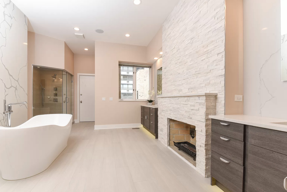 A tub against a marble wall. There is a white brick fireplace mantel.