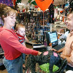 FunDaze \& HoliDaze owner Paul Bowden helps Kristin Elmore and her 1-year-old son Damon with Halloween party decorations.