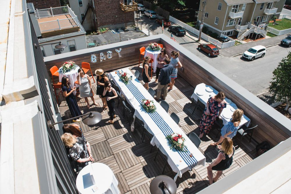 """A restaurant's roof deck in the middle of a city block is set up for a private event with a long table covered in a white tablecloth, blue runner, and floral arrangements. Letter balloons spelling out """"baby"""" hang on one of the deck's wooden walls."""