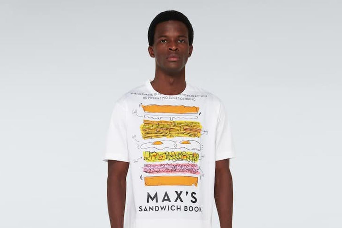 """A male model wears a t-shirt with """"MAX'S SANDWICH BOOK"""" written in black text at the bottom, with a cross-section cartoon of a ham, egg, and chip sandwich"""