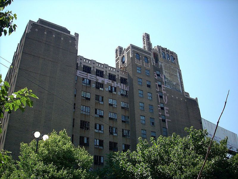 The exterior of the Beury Building in Philadelphia. The facade is brown brick and is in various states of decay. There are many windows.