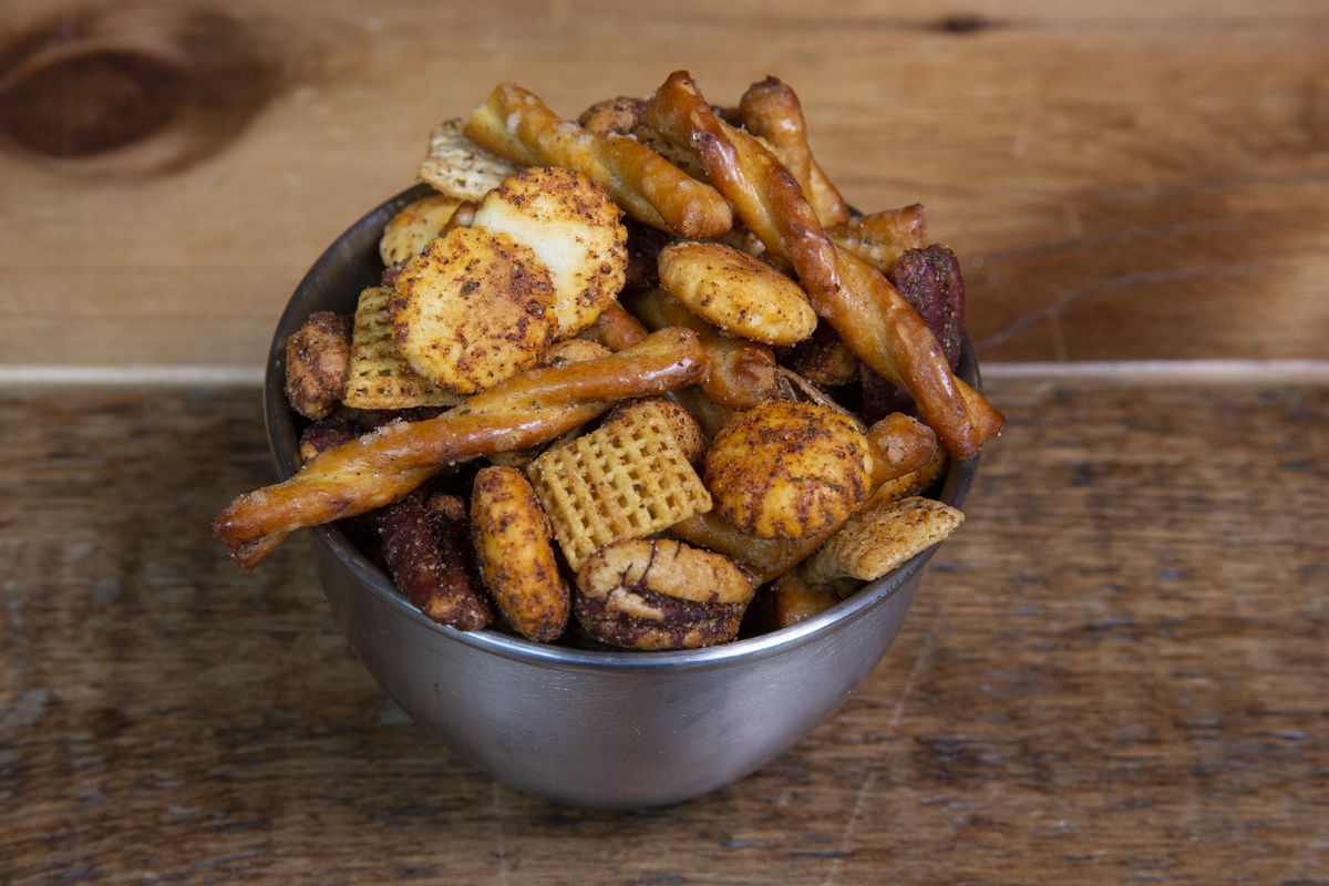 A metal bowl filled with Chex Mix.