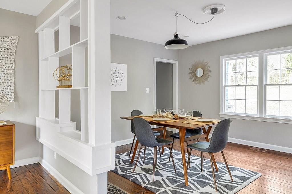A small dining room with a wood table.