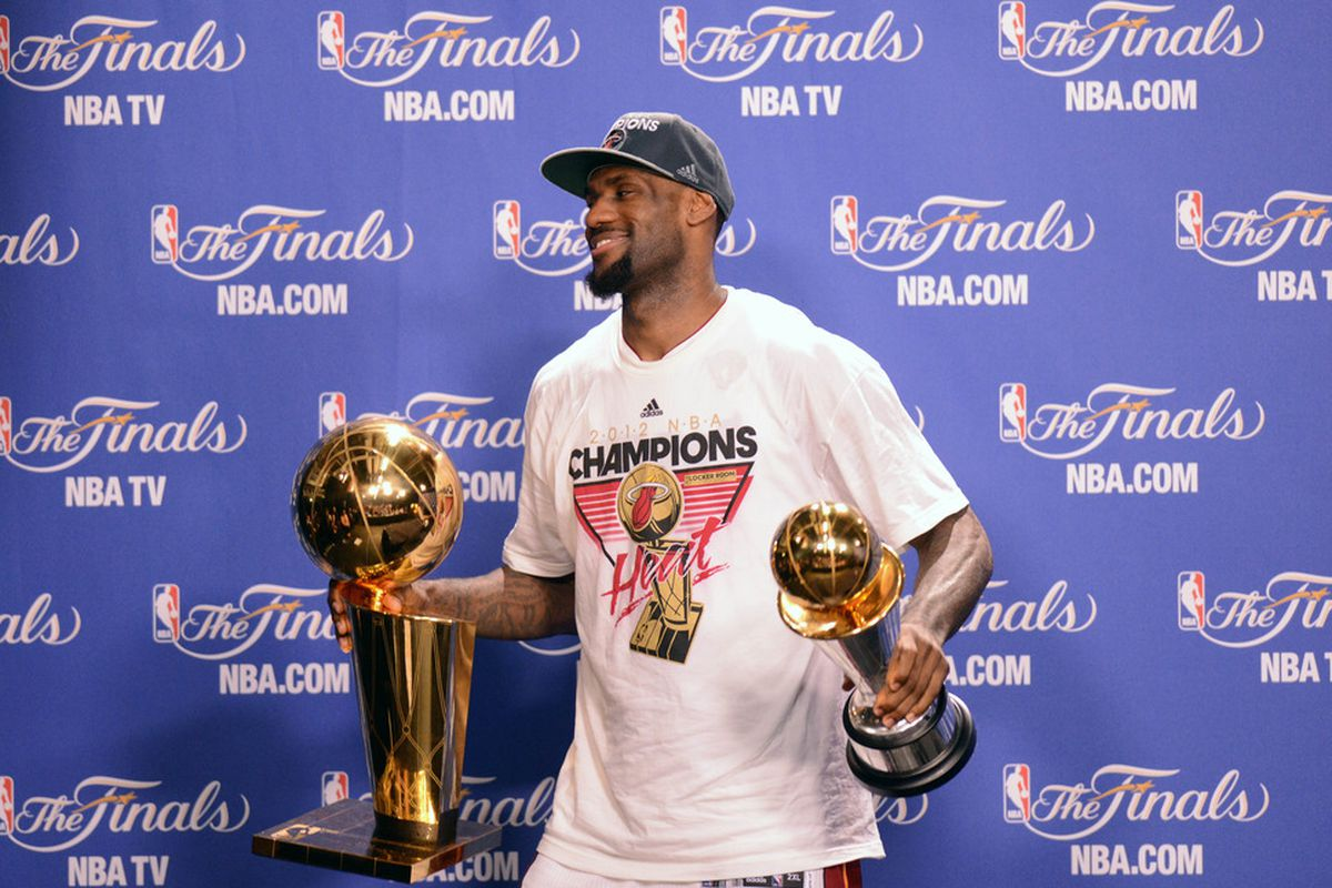 LeBron James holds the NBA championship and Finals MVP trophies.