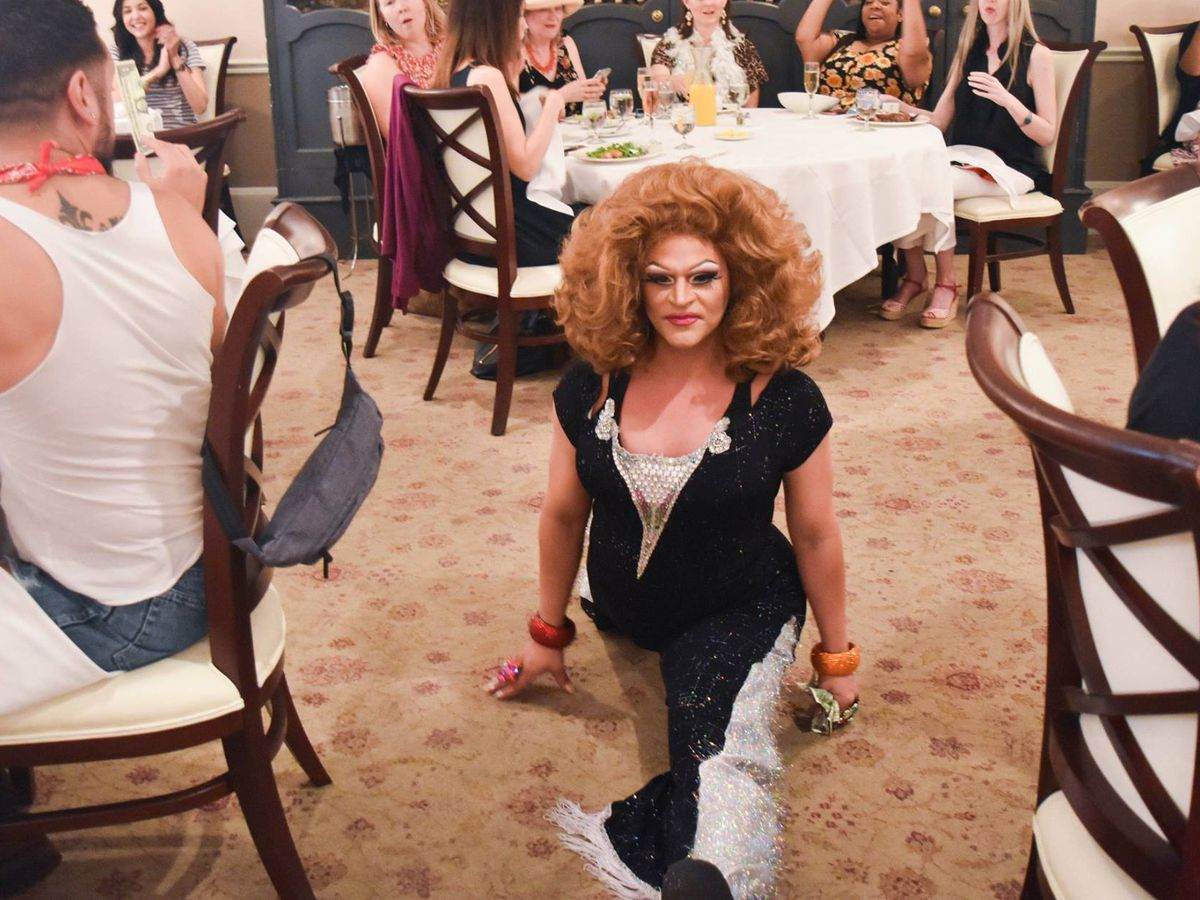 A drag queen does the splits on the floor of Broussard's Restaurant among tables of onlookers