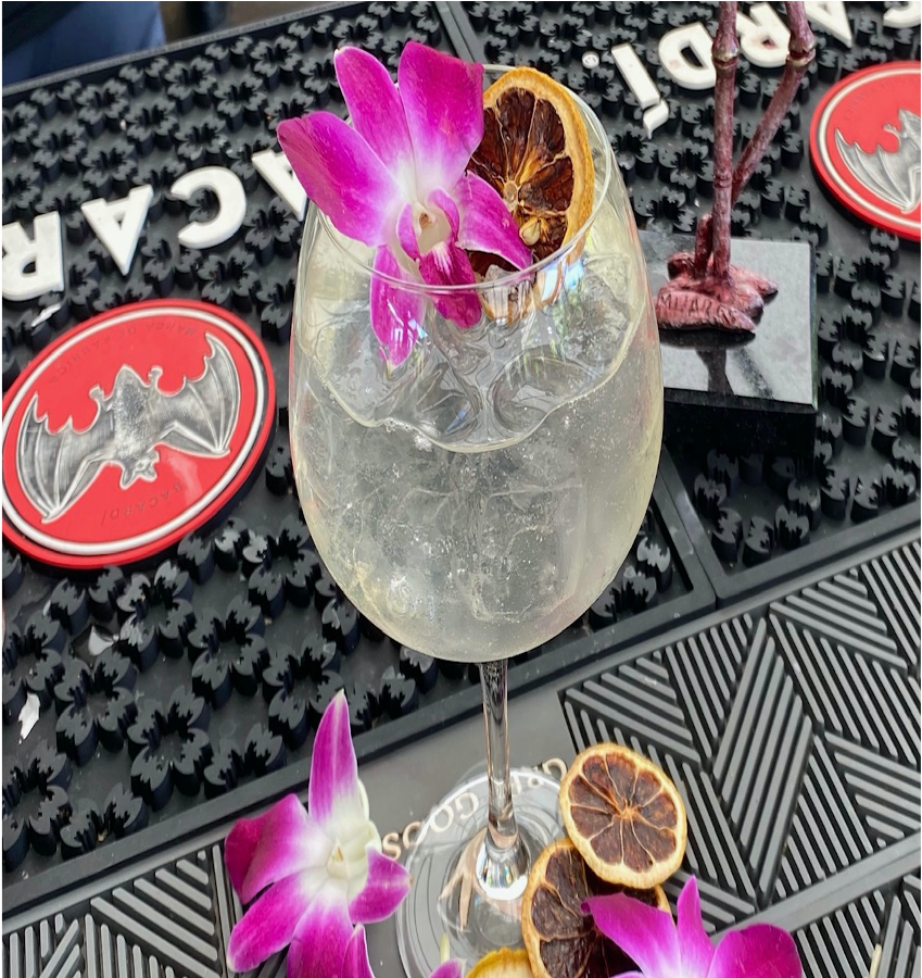 A clear cocktail in a wine glass topped with a purple orchid flower and a dried orange slice