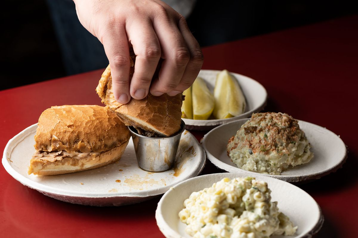 Philippe's, a French dip restaurant, with red tables and a hand dipping a sandwich into jus.