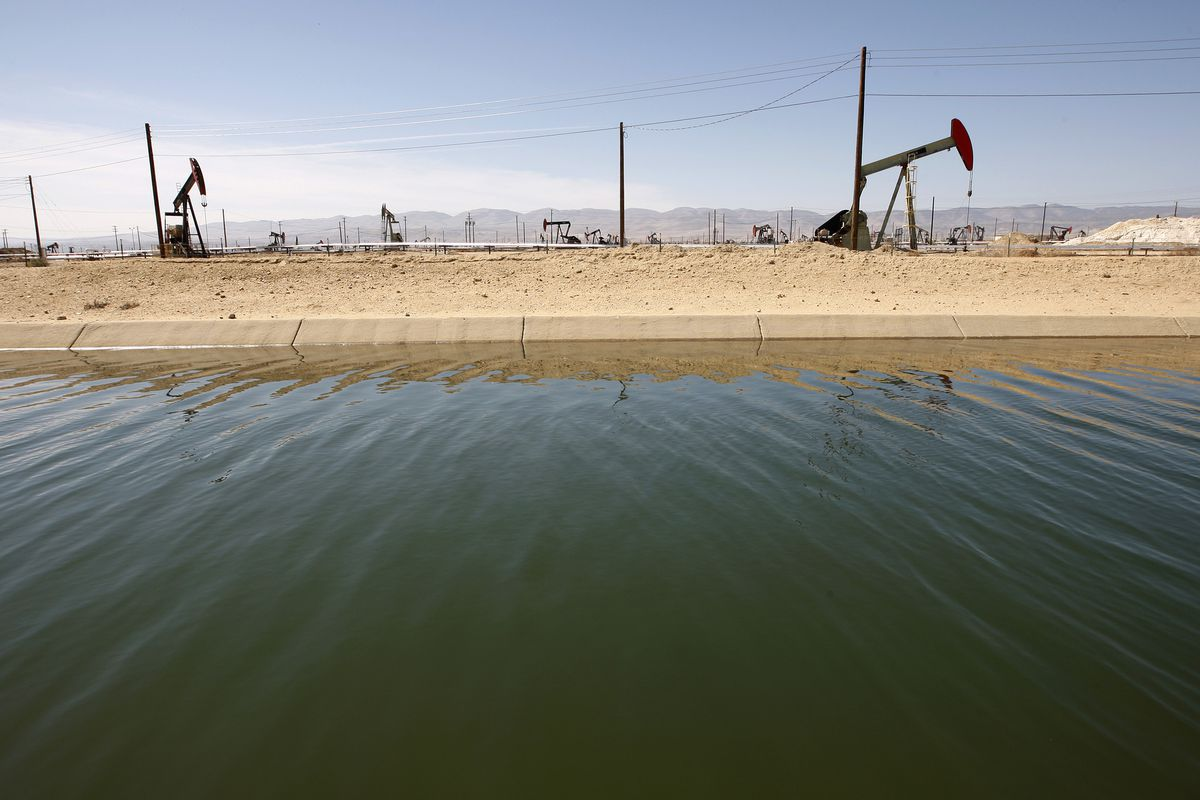 Pump jacks are seen next to a canal in an oil field over the Monterey Shale formation where gas and oil extraction using hydraulic fracturing, or fracking, is on the verge of a boom on March 23, 2014 near Lost Hills, California.