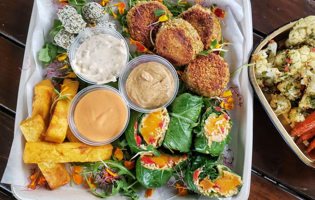 A takeout container full of vegan snacks like vegan crab cakes, collard wraps with roasted butternut squash, fried grit sticks, apple cider glazed carrots, roasted cauliflower, and nut balls
