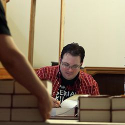 """Brandon Sanderson signs a copy of """"Words of Radiance: Book 2 of the Stormlight Archive"""" at Sam Weller's Bookstore in Salt Lake City on Saturday, Feb. 22, 2014."""