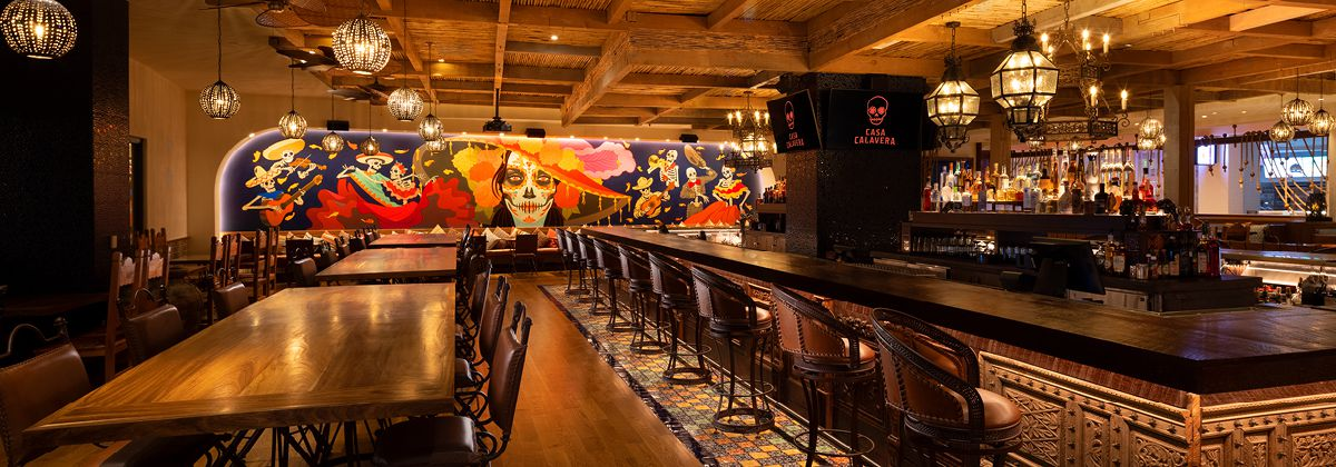 The interior of a Mexican restaurant with a Dia de Muerte skull mural on the wall