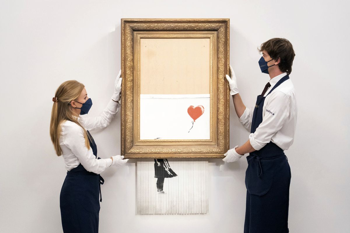 """In this Sept. 3, 2021 file photo, art handlers at Sotheby's auction house hold Banksy's """"Love is in the Bin"""" after it is """"mysteriously"""" shredded following its sale at auction."""