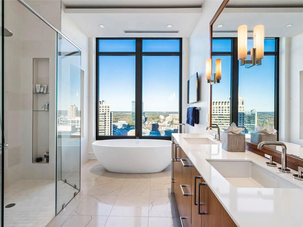 A large white master bathroom with city views.
