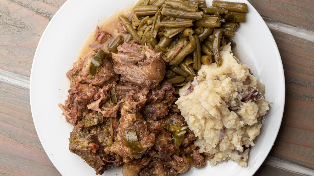 A plate of stewed oxtails with mashed potatoes and green beans.