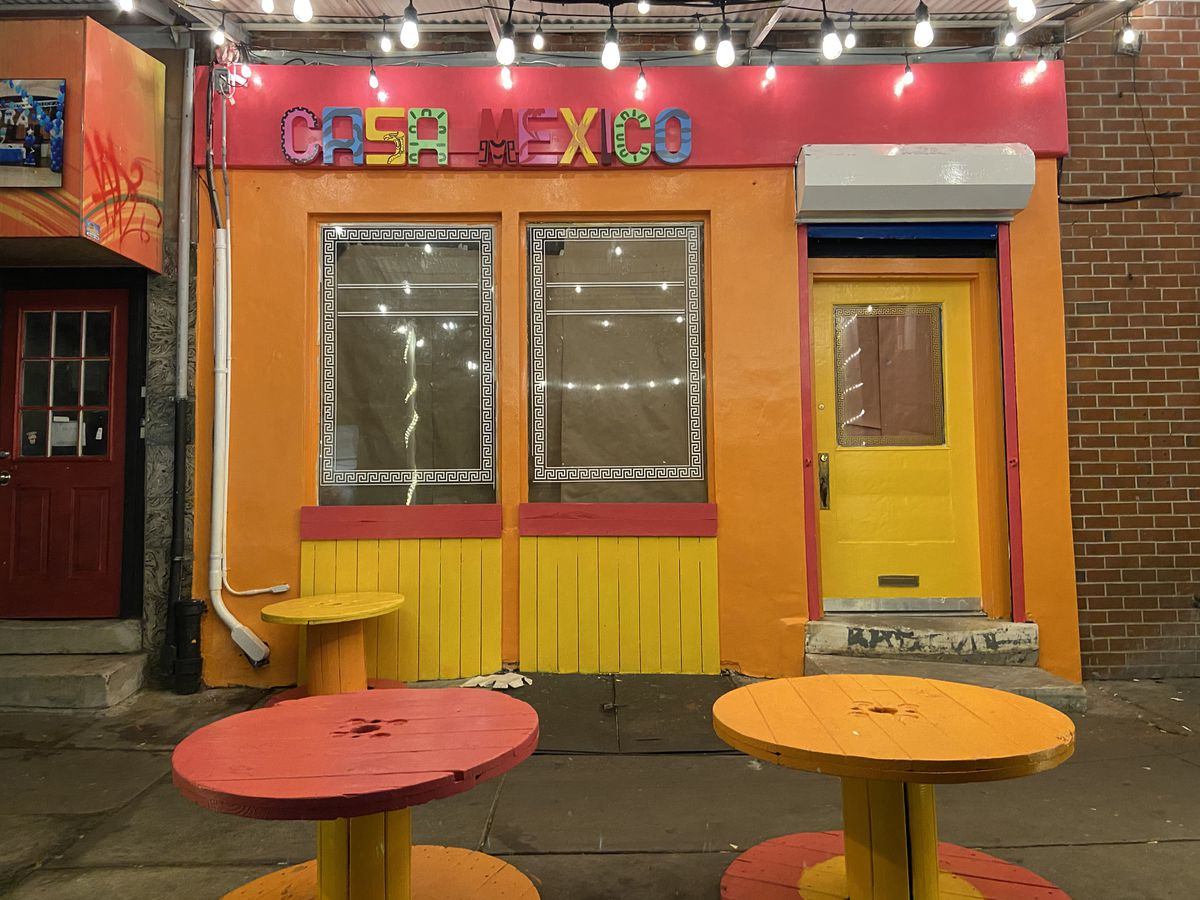 yellow orange and pink storefront with sign that says casa mexico