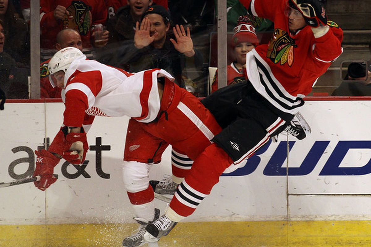 Tomas Kopecky of the Chicago Blackhawks collides with Darren Helm of the Detroit Red Wings at the United Center on December 17 2010 in Chicago Illinois. (Photo by Jonathan Daniel/Getty Images)