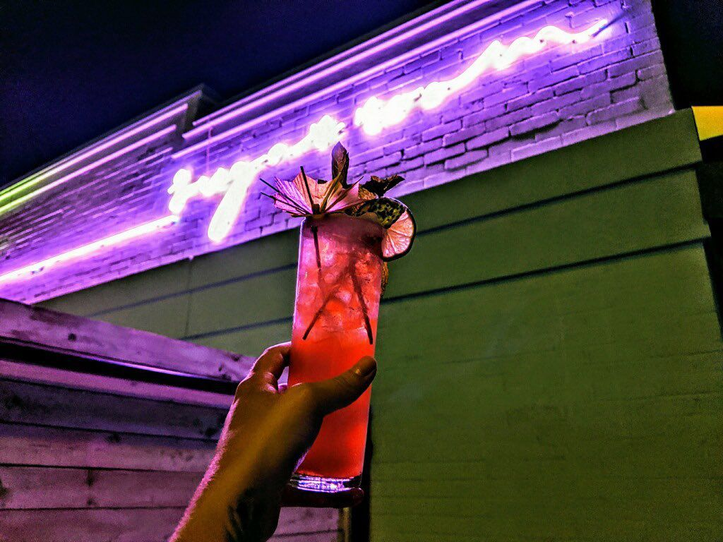 a hand holding up a red cocktail in front of a purple neon sign that reads Sugar Room