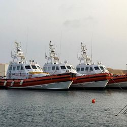 Italian coast guard ships sit ready at the Lampedusa docks. Each can shuttle up to 100 refugees from intercepted or floundering ships or rafts at sea. Sometimes the ships make several rescue trips a day.