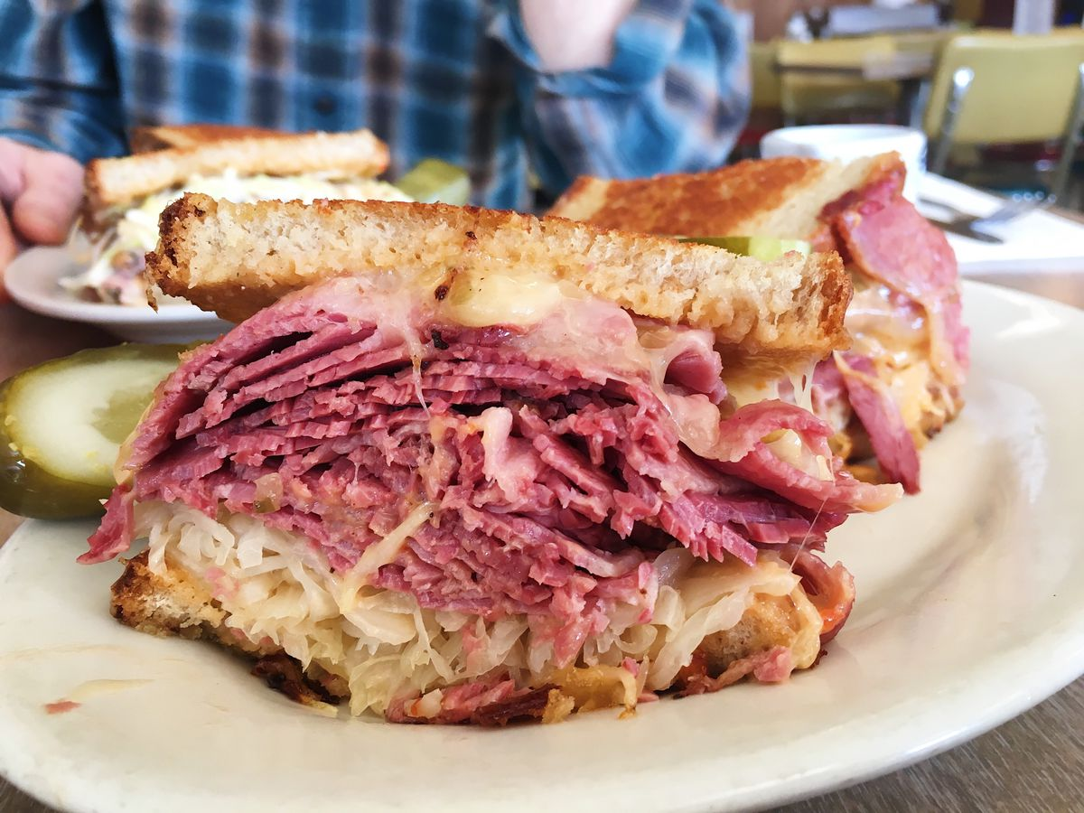 A reuben sandwich from hygrade deli sliced in half with about an inch and a half of corned beef between two slices of toasted bread