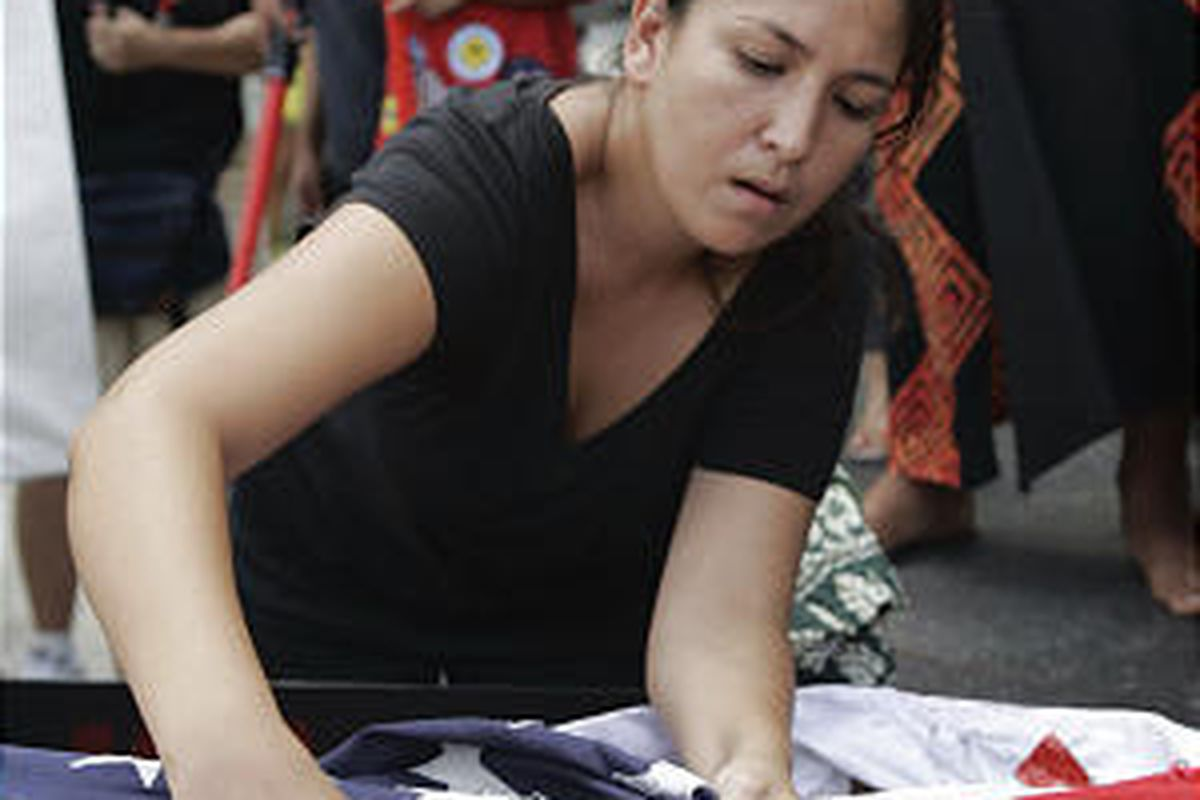 Native Hawaiian activist Jean Stavure cuts a star out of U.S. flag to represent the state during march in Honolulu.