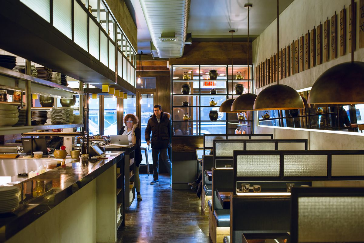 A dining room with booths to the right and a bar to the left, with a person walking into the door in the back.