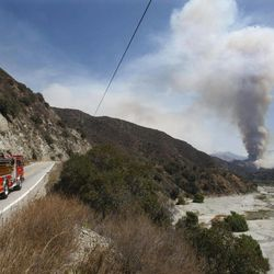 A fire truck heads north on Highway 39 towards a towering plume of smoke in Angeles National Forest, Calif. near Azusa on Tuesday, Sept. 4, 2012.  It could be a week before firefighters can contain the 3,800-acre blaze because of high temperatures and rugged terrain in thick brush that hasn't burned in a couple of decades.