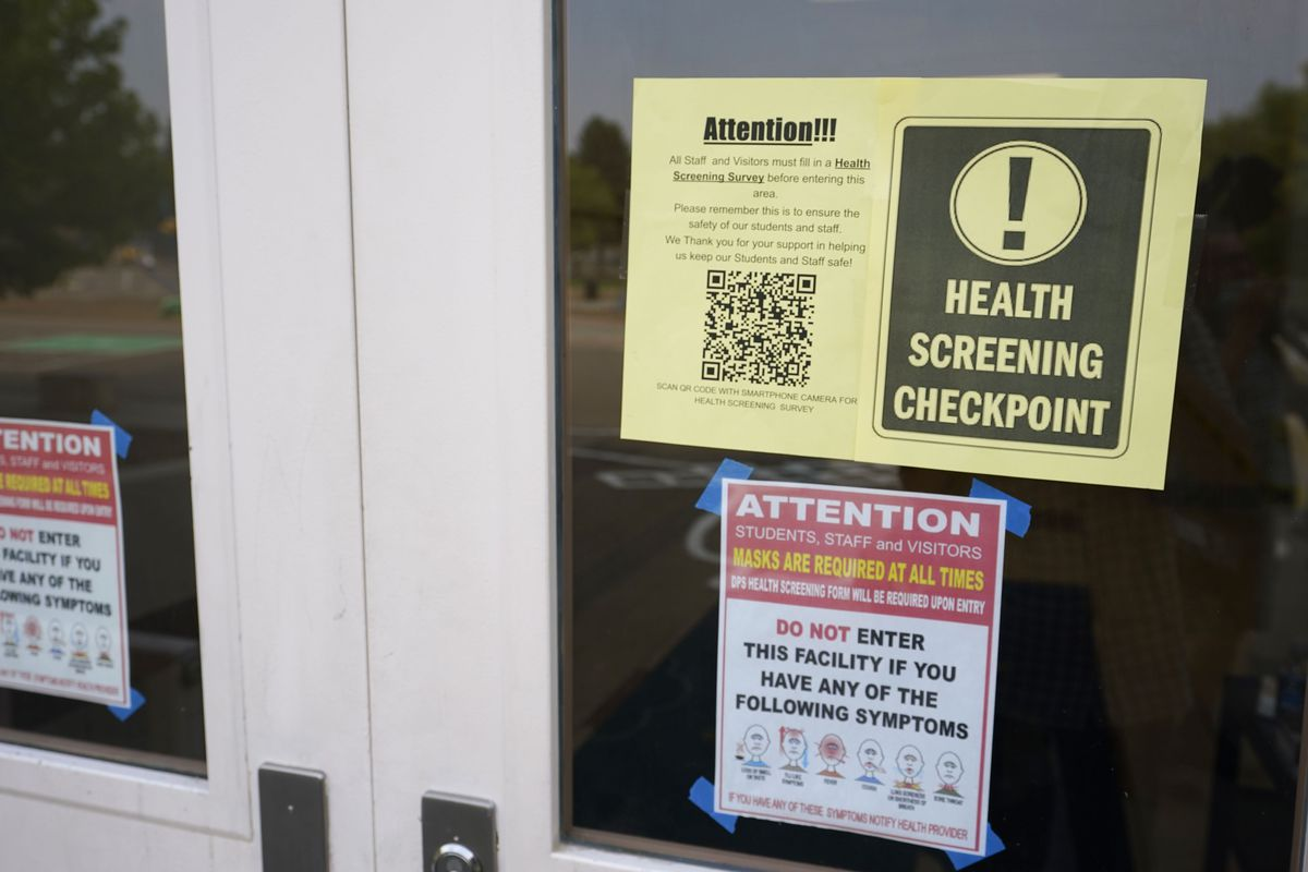 Sign for a health checkpoint hangs in the window of a schoolhouse door.
