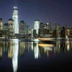 """FILE - In this March 26, 2012, file photo, One World Trade Center towers above the Lower Manhattan skyline and Hudson River in New York. One World Trade Center, the giant monolith being built to replace the twin towers destroyed in the Sept. 11 attacks, will lay claim to the title of New York City's tallest skyscraper on Monday, April 30 as workers erect steel columns that will make its unfinished skeleton a little over 1,250 feet, just high enough to peak over the observation deck on the Empire State Building. The milestone is a preliminary one. The so-called """"Freedom Tower"""" isn't expected to reach its full height for at least another year, at which point it is likely to be declared the tallest building in the U.S."""