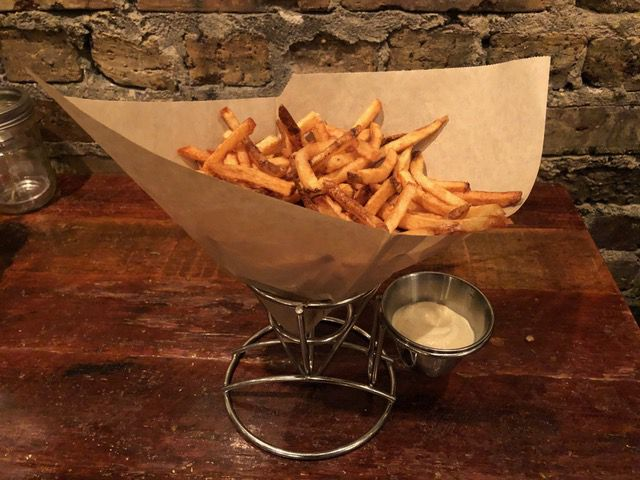 Crispy French fries in a paper basket.