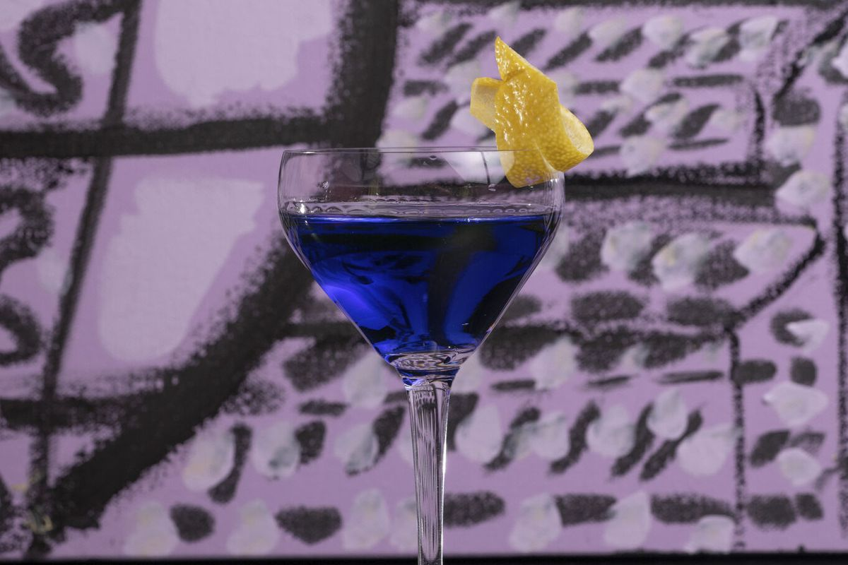 a tall coupe glass holding a royal blue beverage with an orange garnish. the background is a purple wall with black graffiti