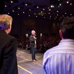 Salt Lake Comic Con co-founders Dan Far and Bryan Brandenburg listen as Sir Patrick Stewart addresses the crowd at a FanX event.