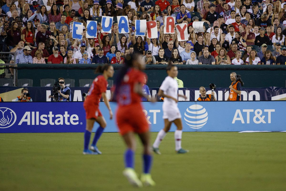 In this Aug. 29, 2019, file photo, fans hold up a sign for equal pay during the second half of an international friendly soccer match between the United States and Portugal in Philadelphia.