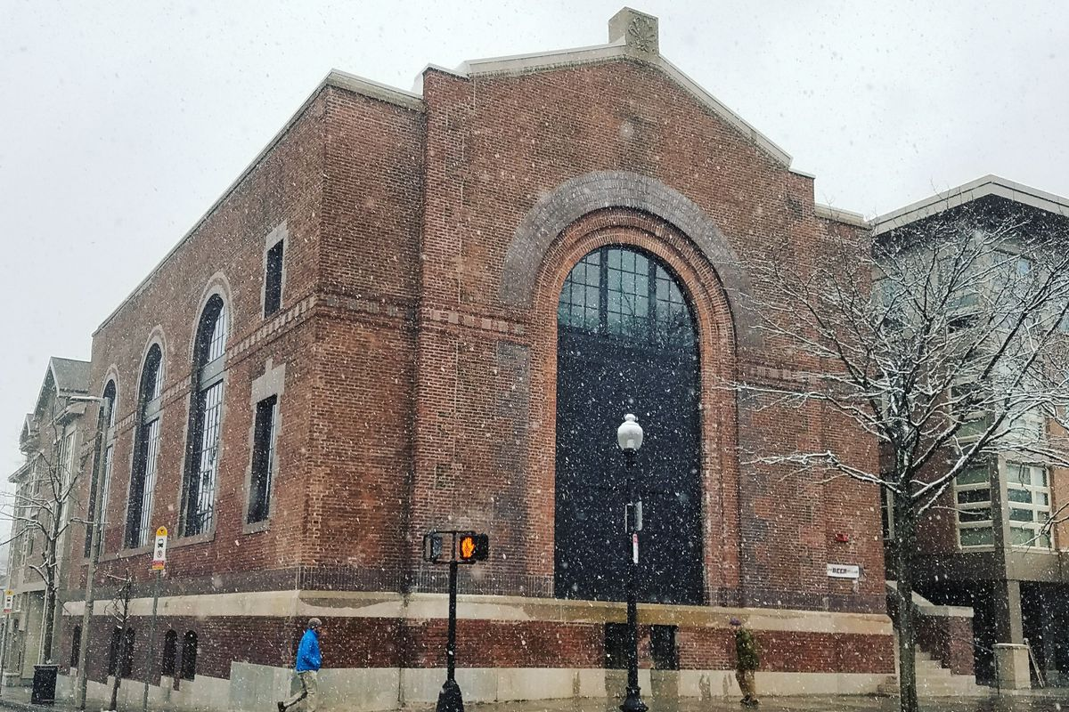 A sort of monolithic-looking brick building with large arched windows in the front and on the side.