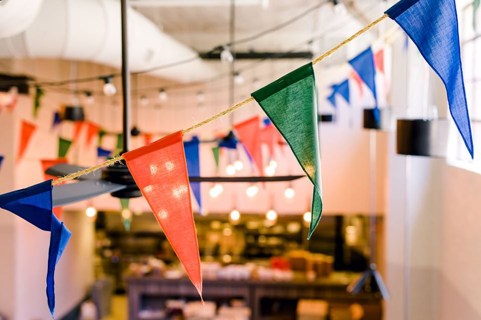A string of colorful cotton flags hanging above the dining room at Rina in Atlanta