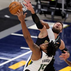 Utah Jazz center Derrick Favors (15) battles Memphis Grizzlies center Jonas Valanciunas (17) for a rebound as the Utah Jazz and the Memphis Grizzlies play in game one of their NBA playoff series at Vivint Arena in Salt Lake City on Sunday, May 23, 2021.