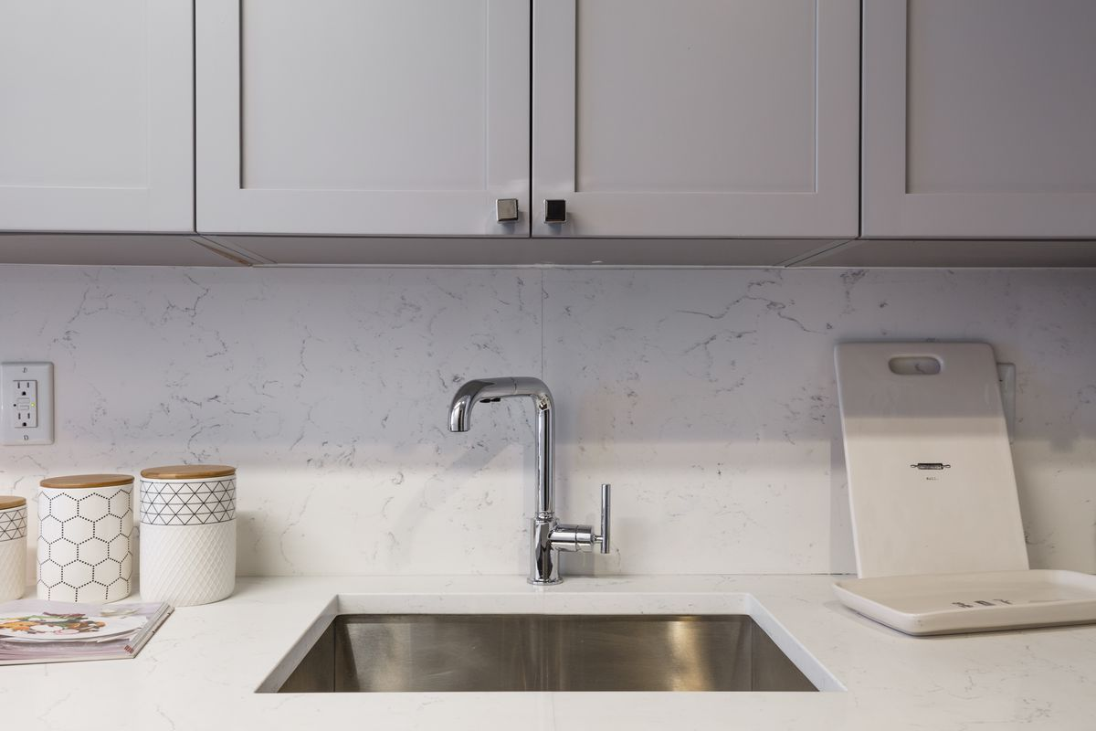A kitchen sink surrounded by marble countertops.