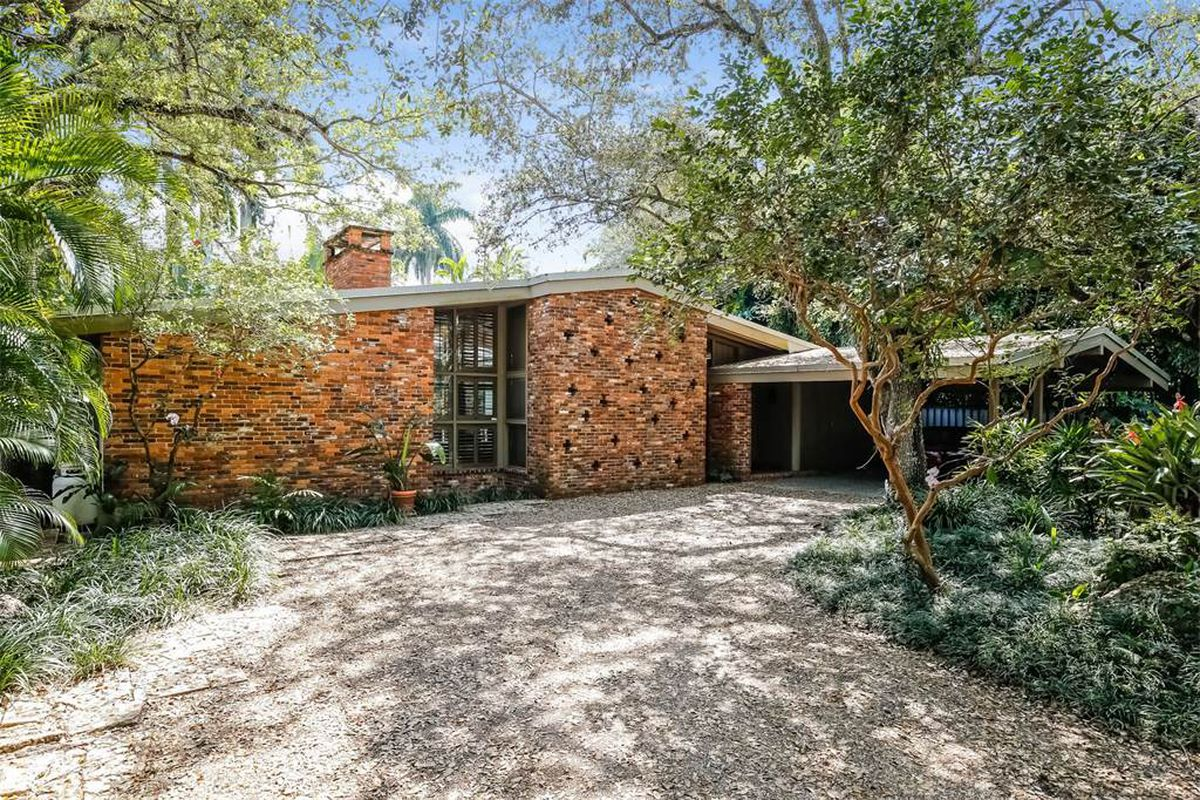 One story home with brick facade and cross cutouts with a broad sloping roof and carport set among a leafy lot.