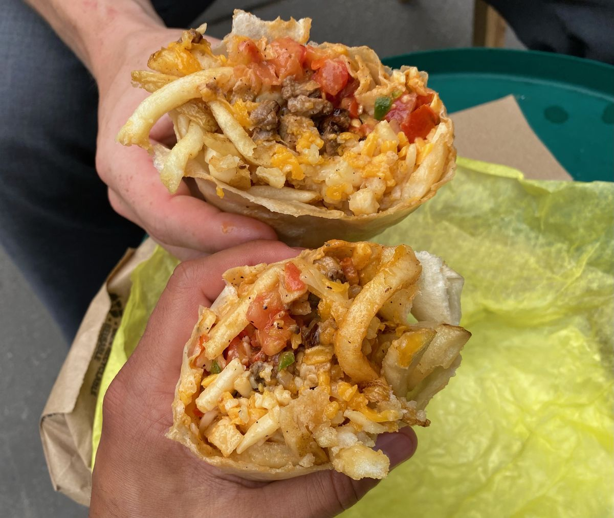 Two hands hold two halves of a California burrito, stuffed with rice, pico de gallo, French fries, and carne asada