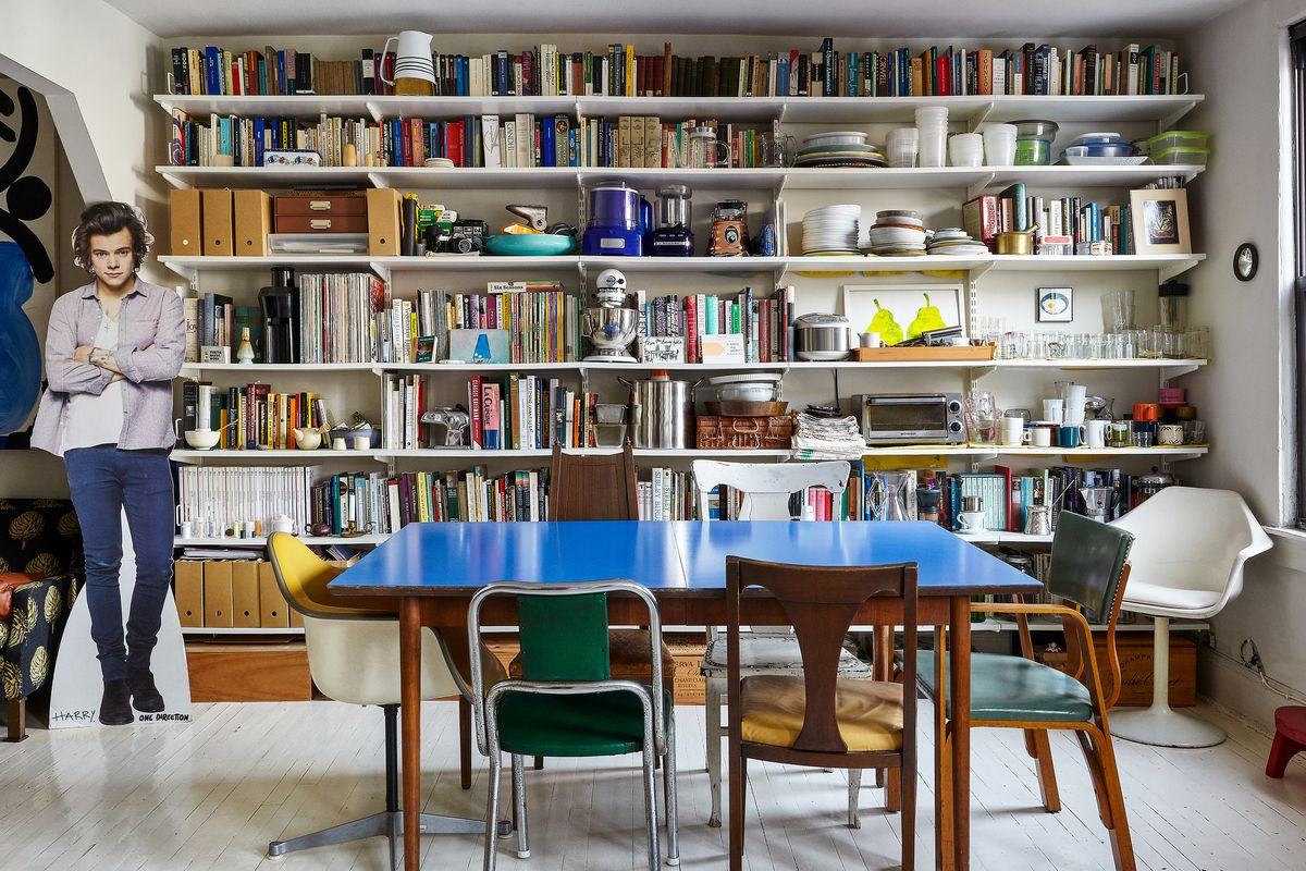 A dining area. There is a large blue dining room table surrounded by multiple chairs of various design. Against the wall are floor to ceiling bookshelves full of books, ceramics, artwork, and other household items.