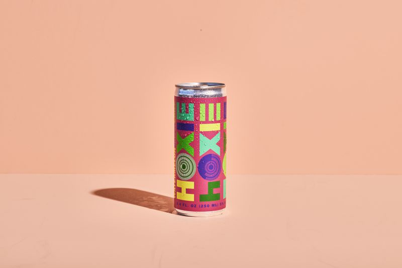 """Aluminum can with dark pink label and """"Hoxie Moxie"""" written in a multicolor, blocky typeface."""