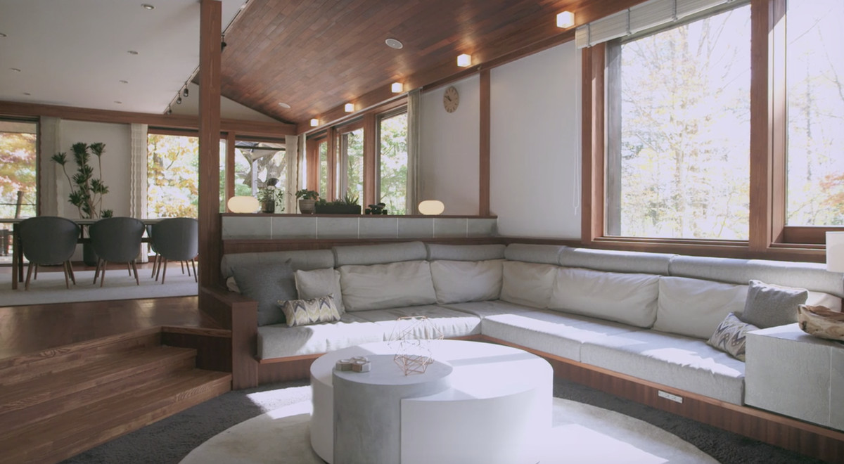 In the foreground is a white couch and a table. There are pillows on the couch. In the background is a dining room with a table and chairs. There are windows along the walls. The floor is hardwood.