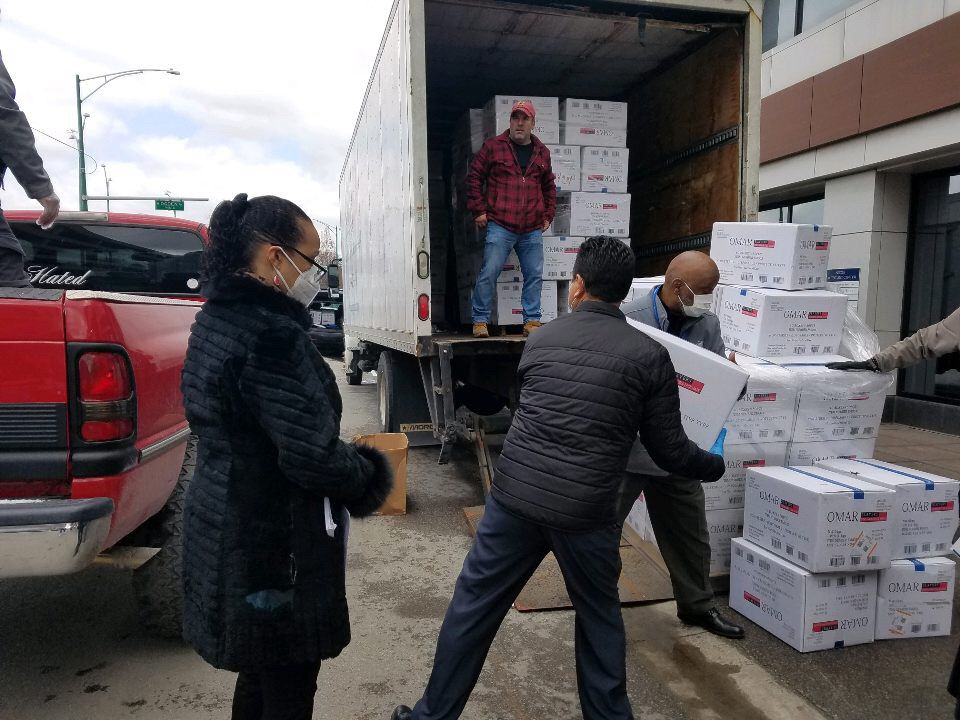 Brighton Park Neighborhood Council staff unload a shipment of donated face masks.