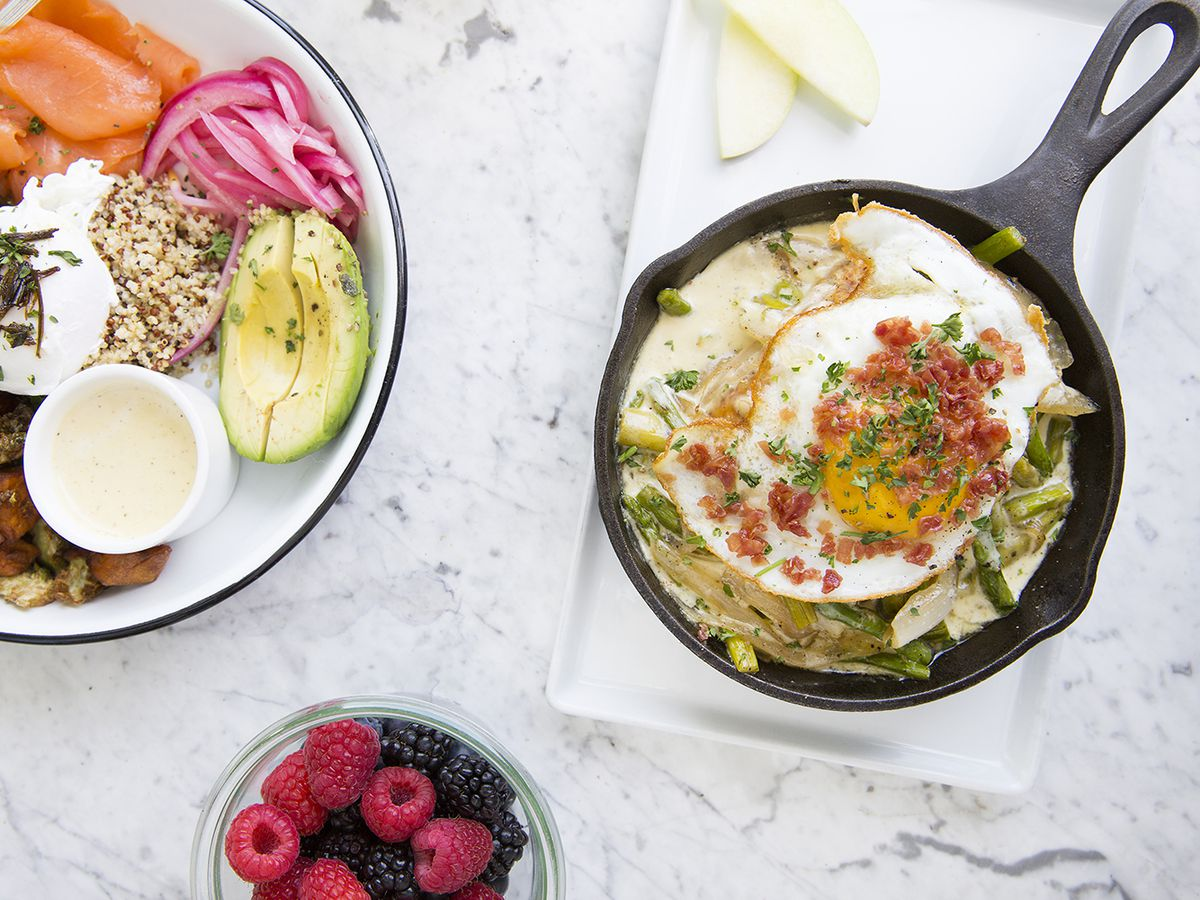 From above, a table laid with several items. There's a plate with a sampler dish of breakfast grains, avocado, pickles, greens, and sweet potato. There's also a skillet with cheesy vegetables and a fried egg