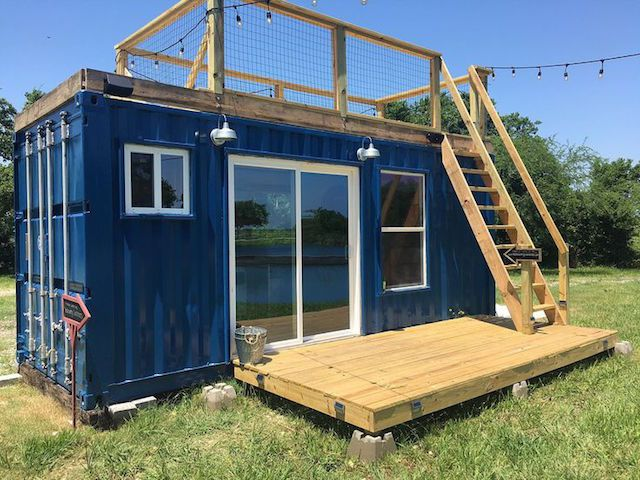 A small shipping container that has been converted into a home. There is a door, windows, deck, and a wooden staircase leading to a roof deck. The exterior is painted blue.