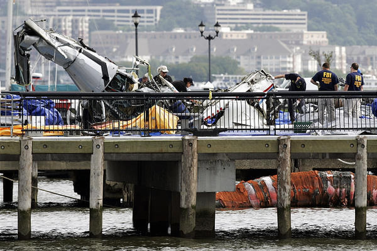 Investigators examine the wreckage of an airplane, right, that sits on a pier next to the the wreckage of a helicopter Wednesday in Hoboken, N.J. The two aircraft collided and fell into the Hudson River on Saturday killing ine people died including three