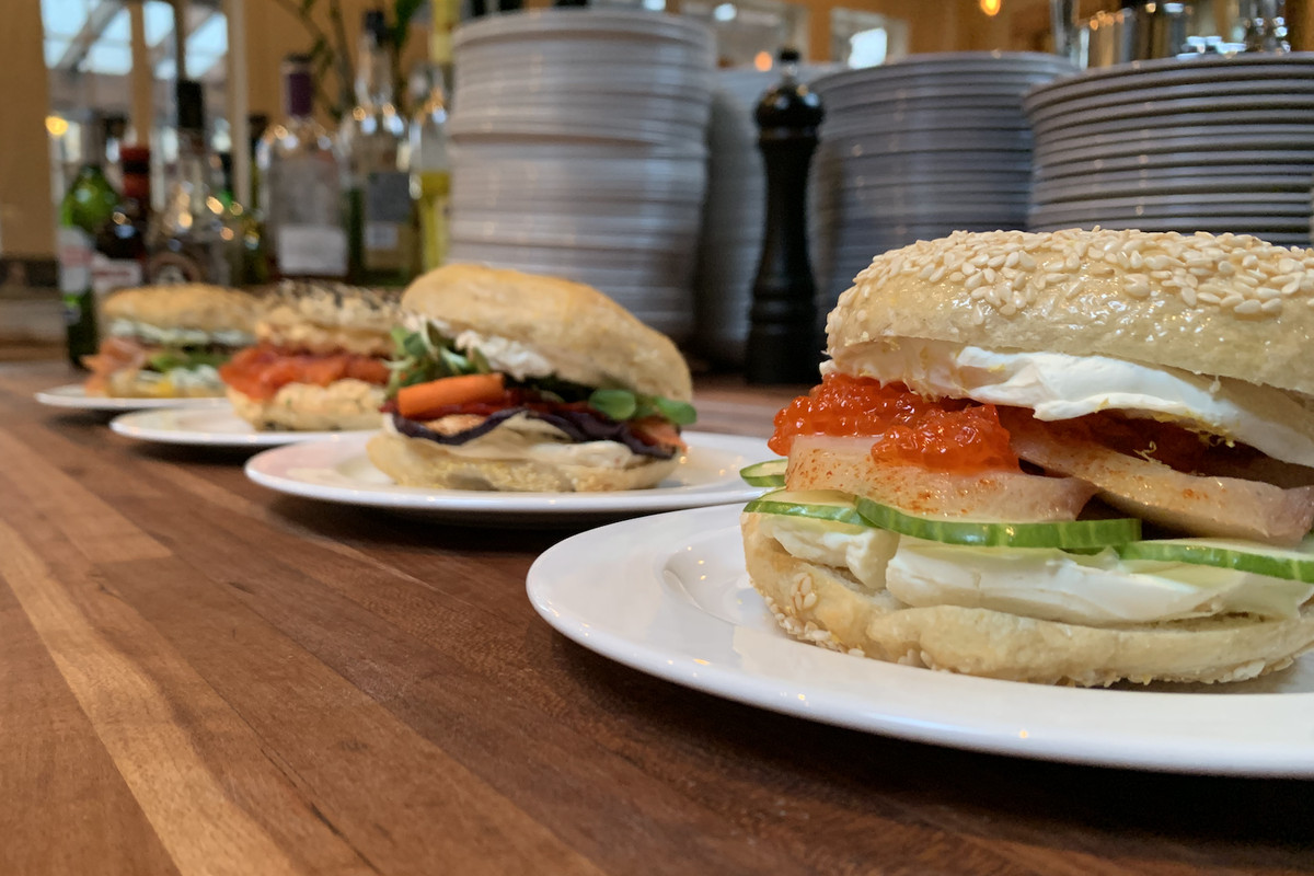 Bagel sandwiches lined up on a counter, stuffed with smoked fish and cream cheese